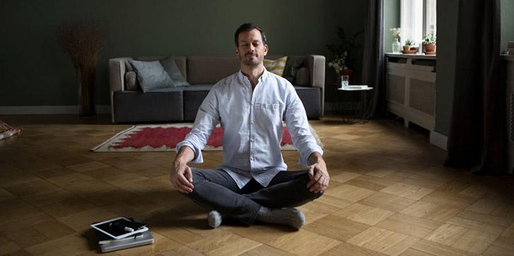 Uomo in meditazione seduto sul pavimento