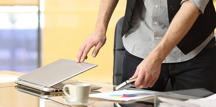 Uomo che chiude laptop per iniziare digital detox