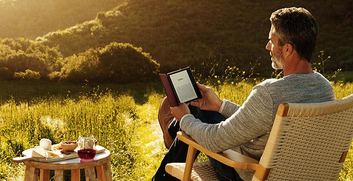 Uomo che legge il suo kindle in mezzo alla natura