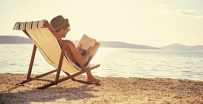 Ragazzo che legge sulla spiaggia