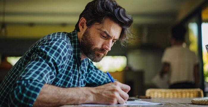 Uomo che scrive il proprio diario ad una scrivania