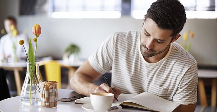 Uomo che scrive il proprio diario seduto in un bar